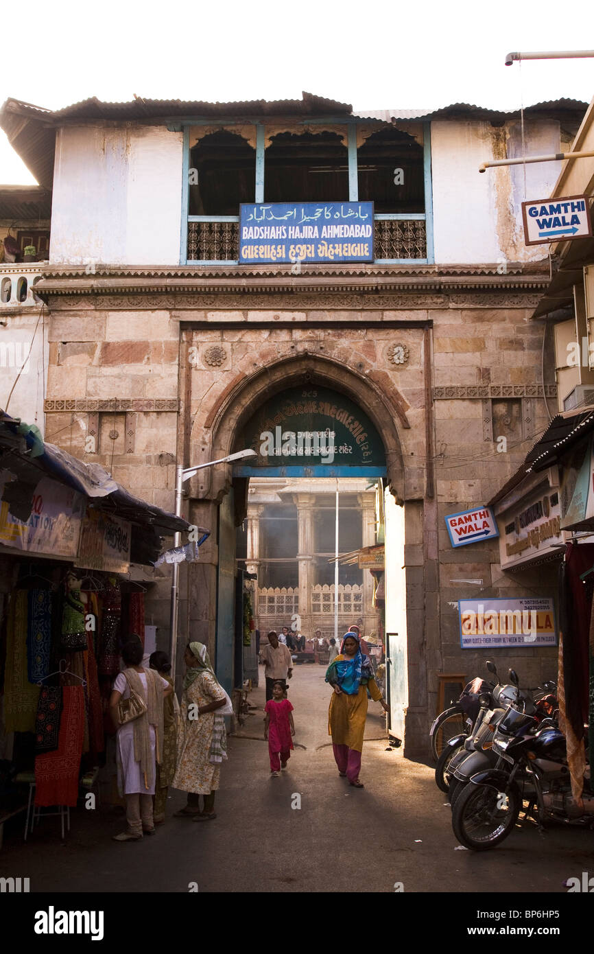 Women look at clothing while others walk through the gate to Badshah's Hajira in the old city of Ahmedabad, - Stock Image