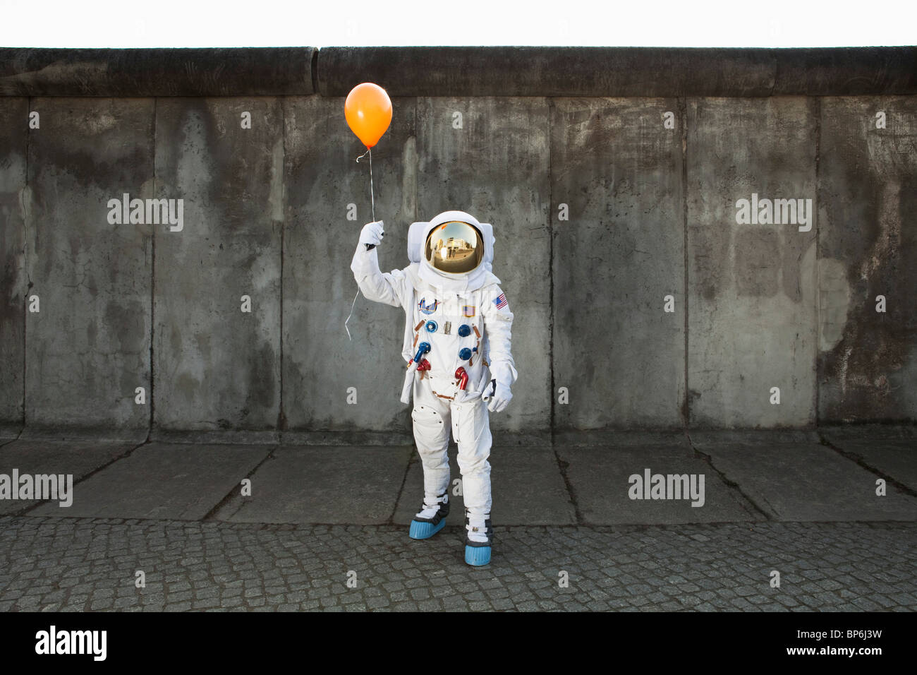 An astronaut on a city sidewalk holding a balloon - Stock Image