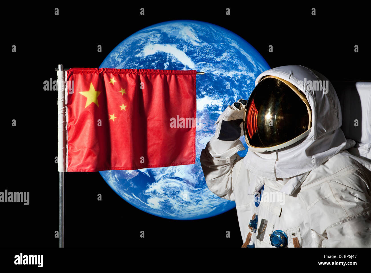 An astronaut saluting an Chinese flag with the earth in the background - Stock Image