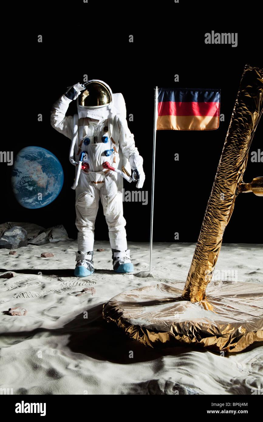 An astronaut standing near a lunar lander salutes an German flag - Stock Image