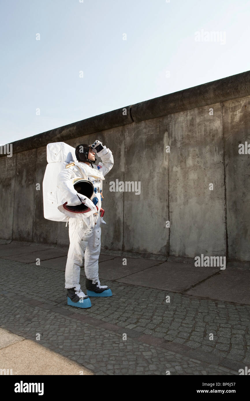 An astronaut on a city sidewalk looking up into the sky Stock Photo