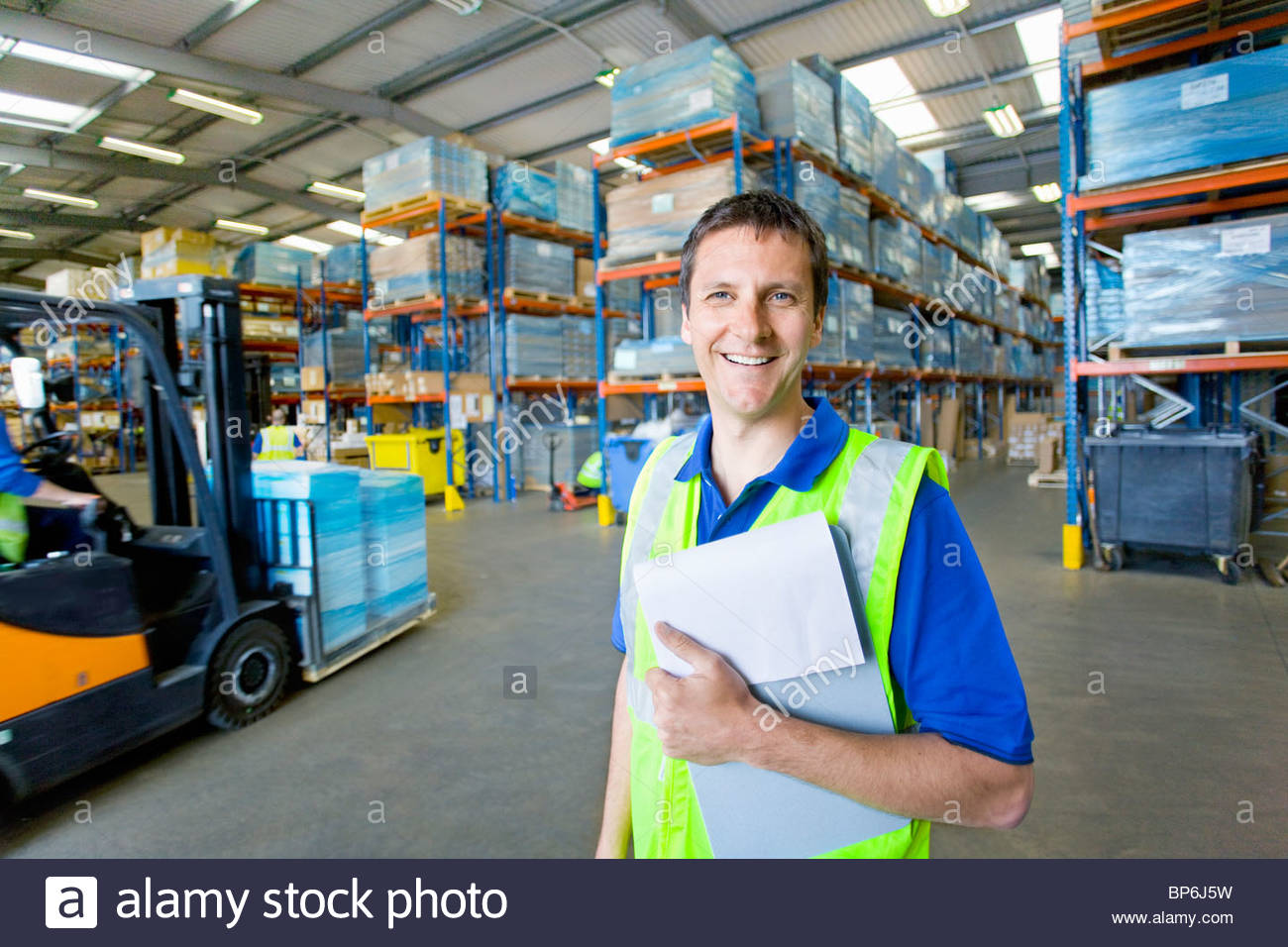 Worker in warehouse holding clipboard - Stock Image