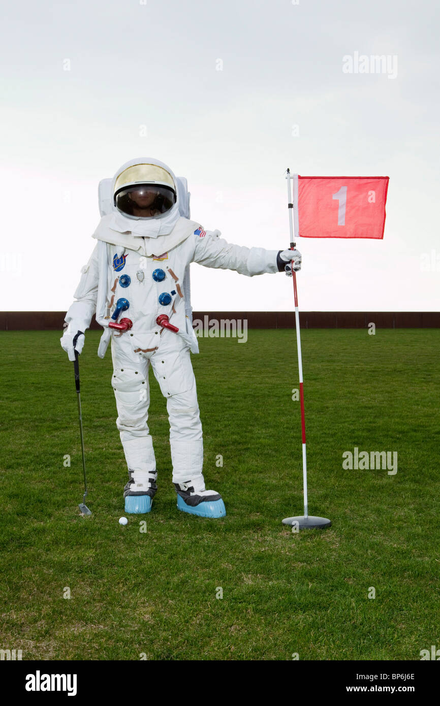 An astronaut posing on a putting green - Stock Image
