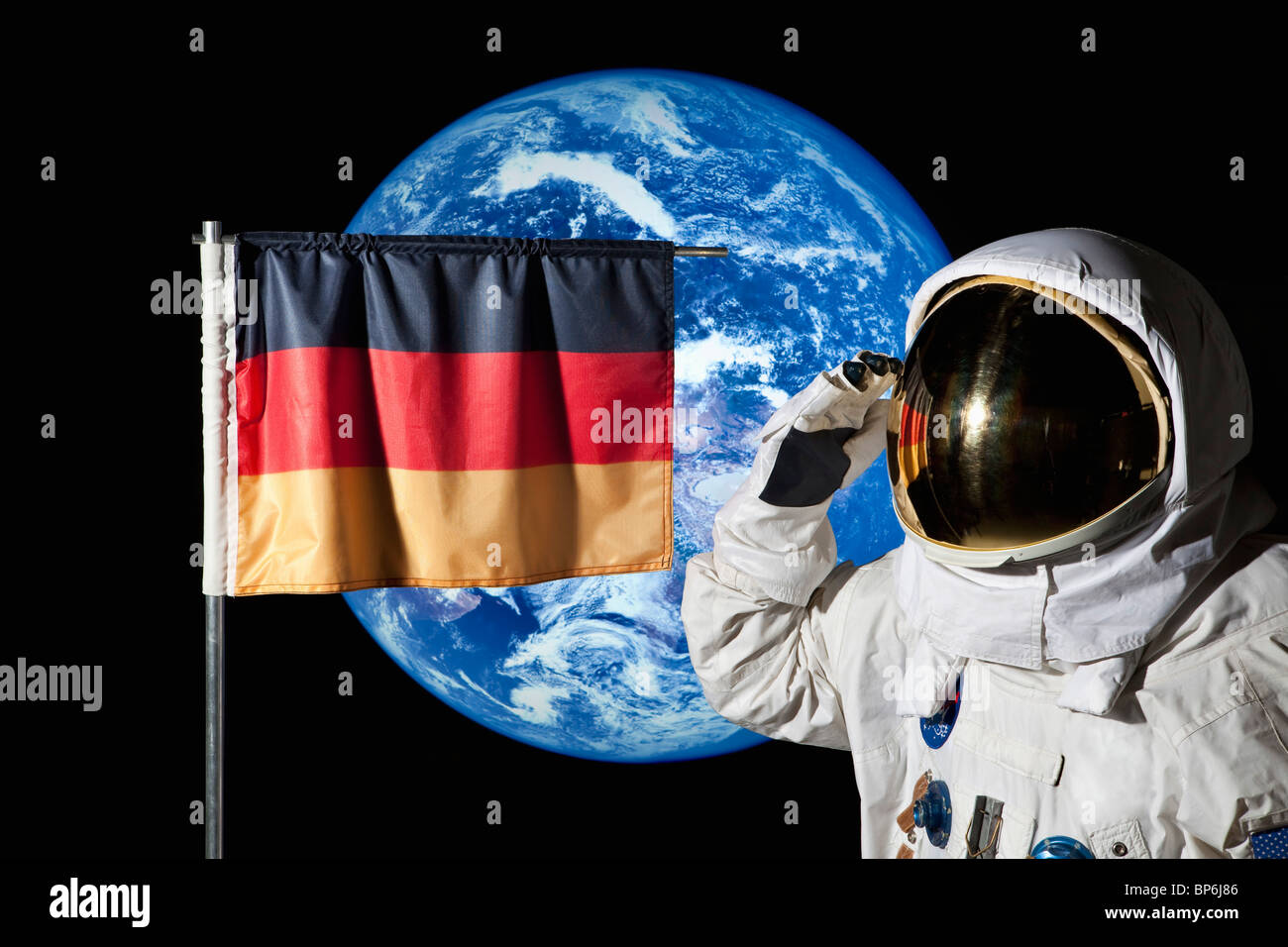 An astronaut saluting an German flag with the earth in the background - Stock Image