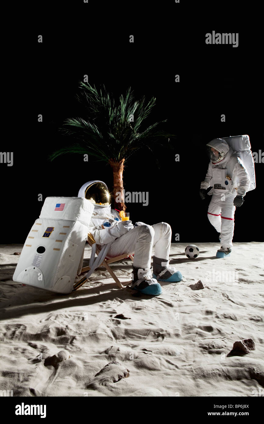 Two astronauts on the moon enjoying some leisure time - Stock Image