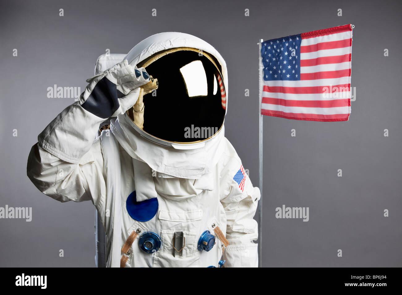 An astronaut saluting next to an American flag, studio shot - Stock Image