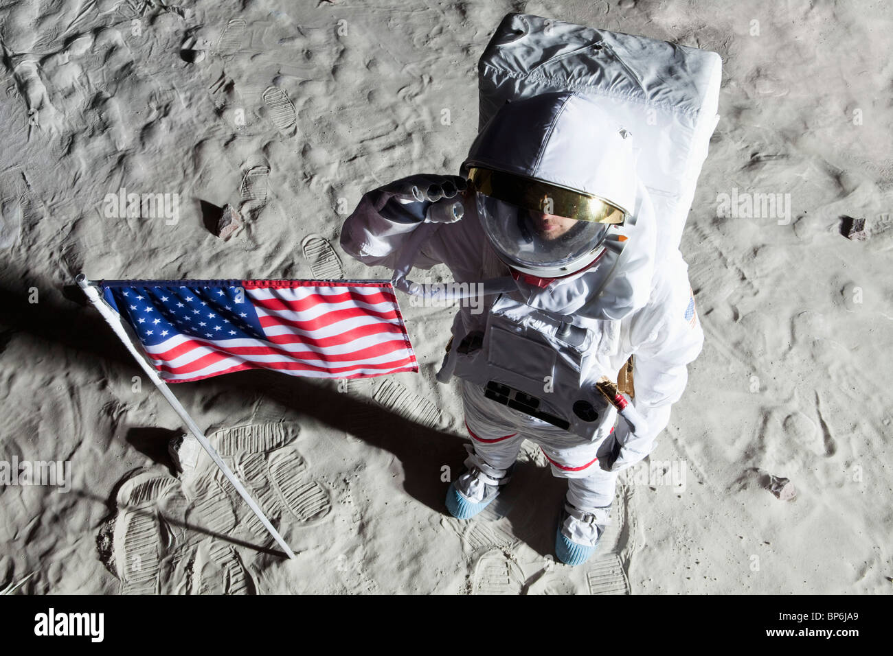 An astronaut on the surface of the moon saluting an American flag - Stock Image