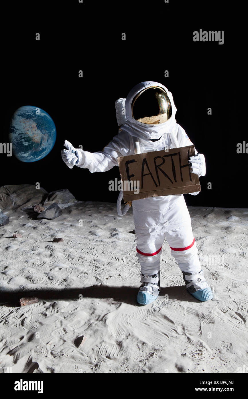 An astronaut on the moon with his thumb out, holding 'EARTH' sign - Stock Image