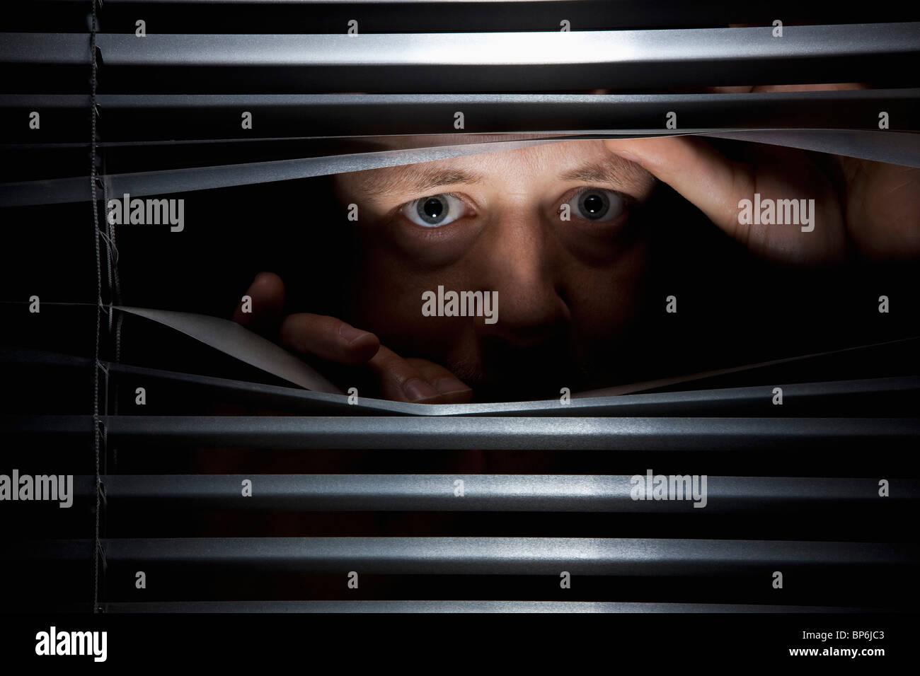 A man peeking through blinds - Stock Image