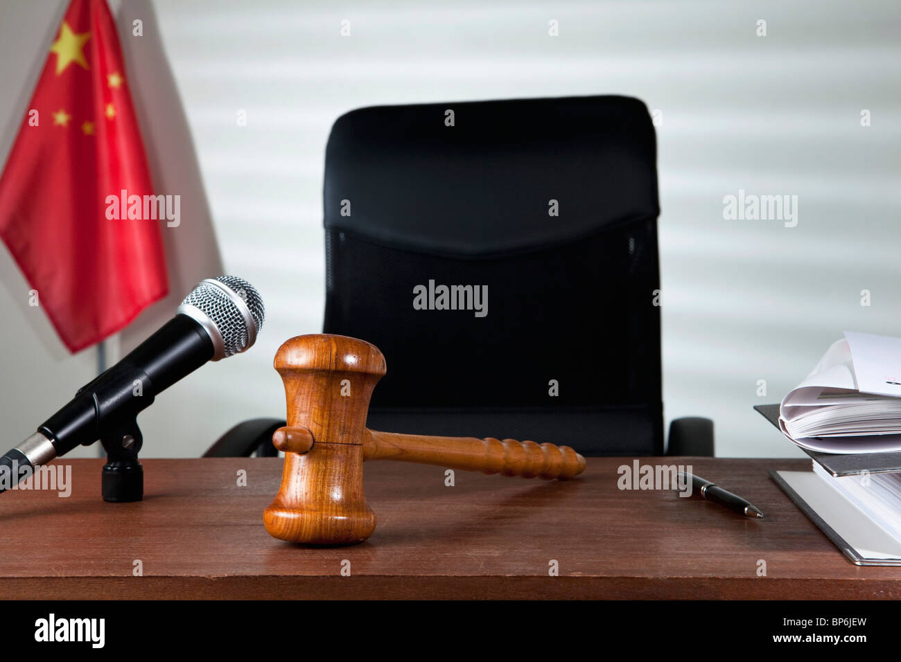 A gavel on a judge's desk in an empty courtroom - Stock Image