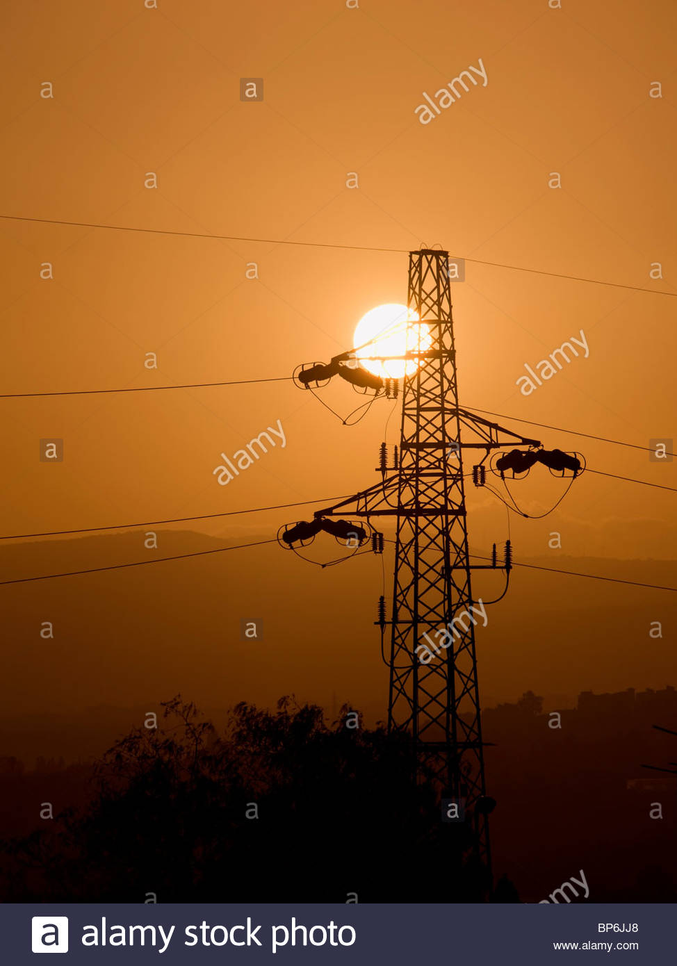 Electricity pylon silhouetted against sky at sunset, Sicily, Italy - Stock Image