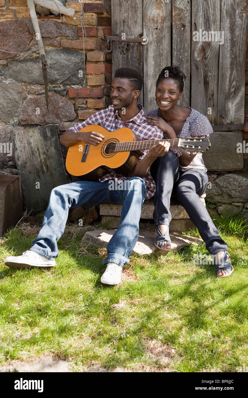 A man playing an acoustic guitar with his girlfriend Stock Photo