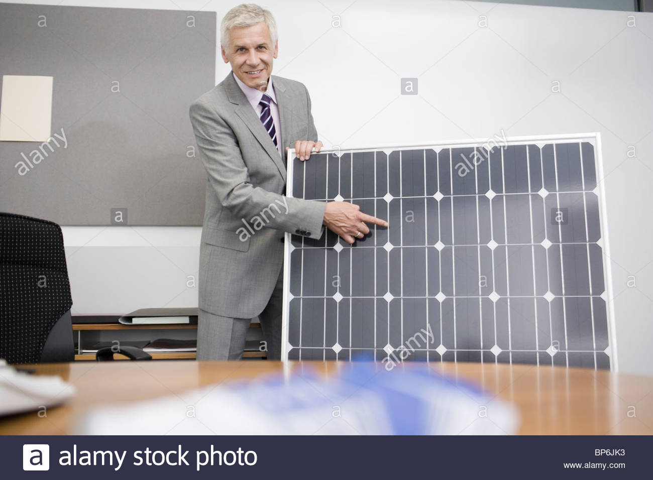 A mature businessman in an office demonstrating a solar panel - Stock Image