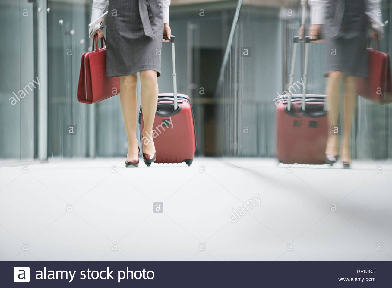 A businesswoman walking along a corridor pulling a suitcase - Stock Image