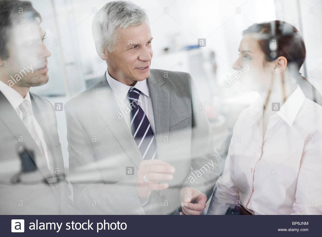 Three businesspeople talking - Stock Image