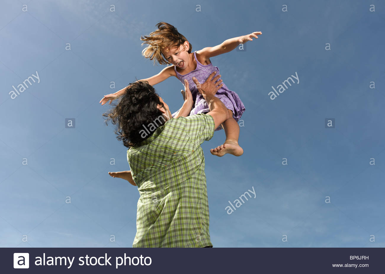 A father throwing his daughter in the air - Stock Image