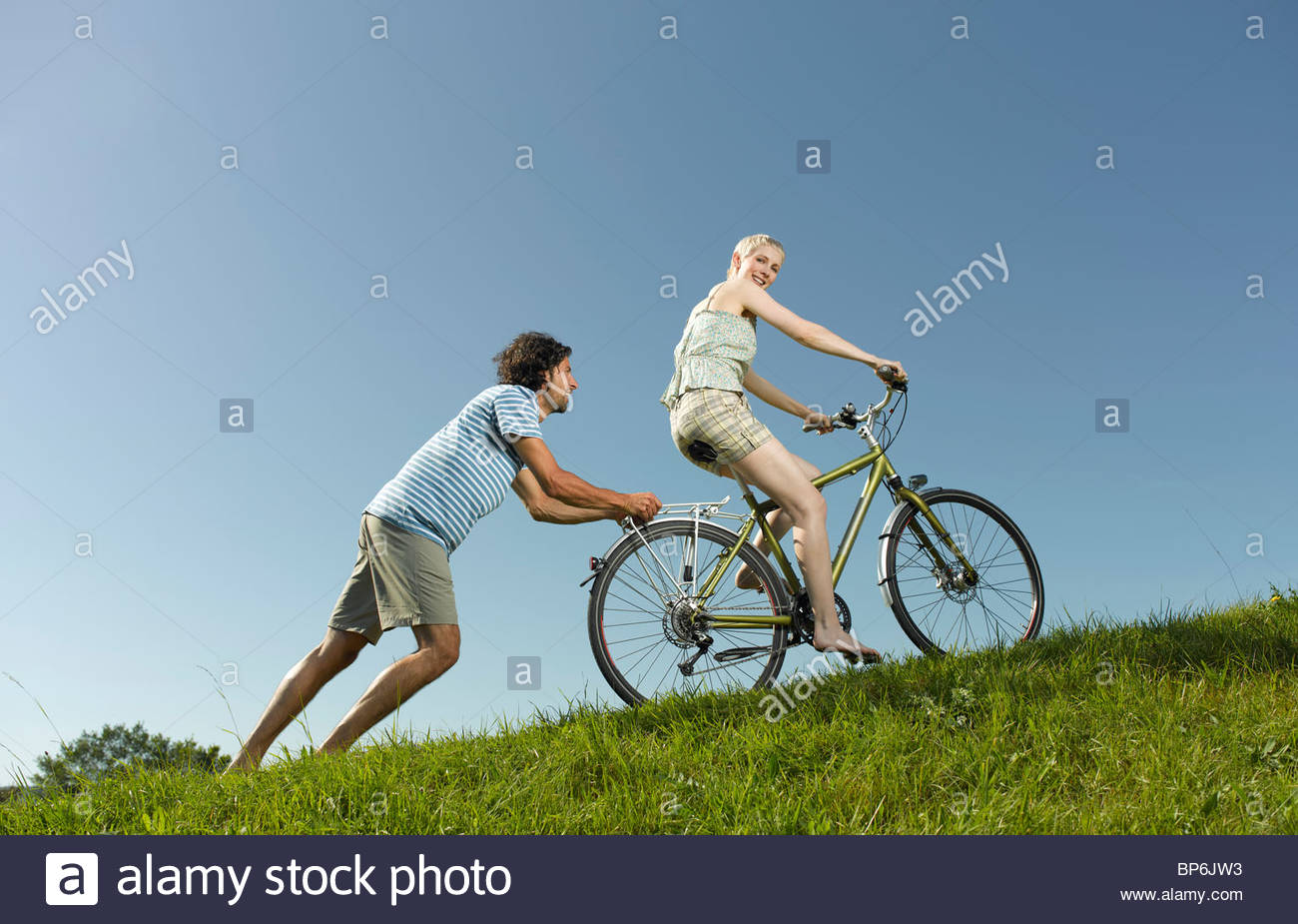 A woman on a bicycle, man pushing her uphill - Stock Image