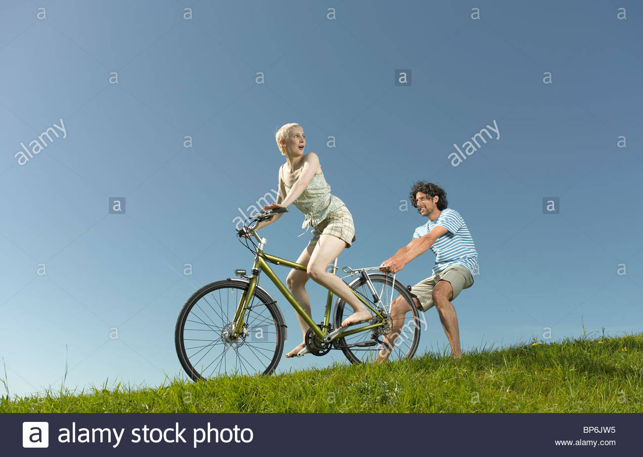 A woman on a bicycle, man holding onto the back - Stock Image