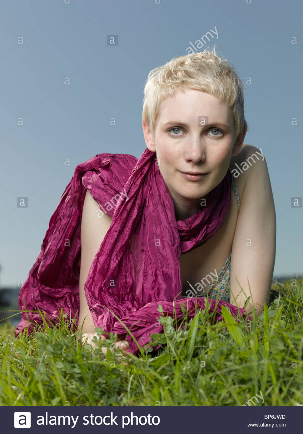 A young woman lying in the grass wearing a magenta scarf - Stock Image