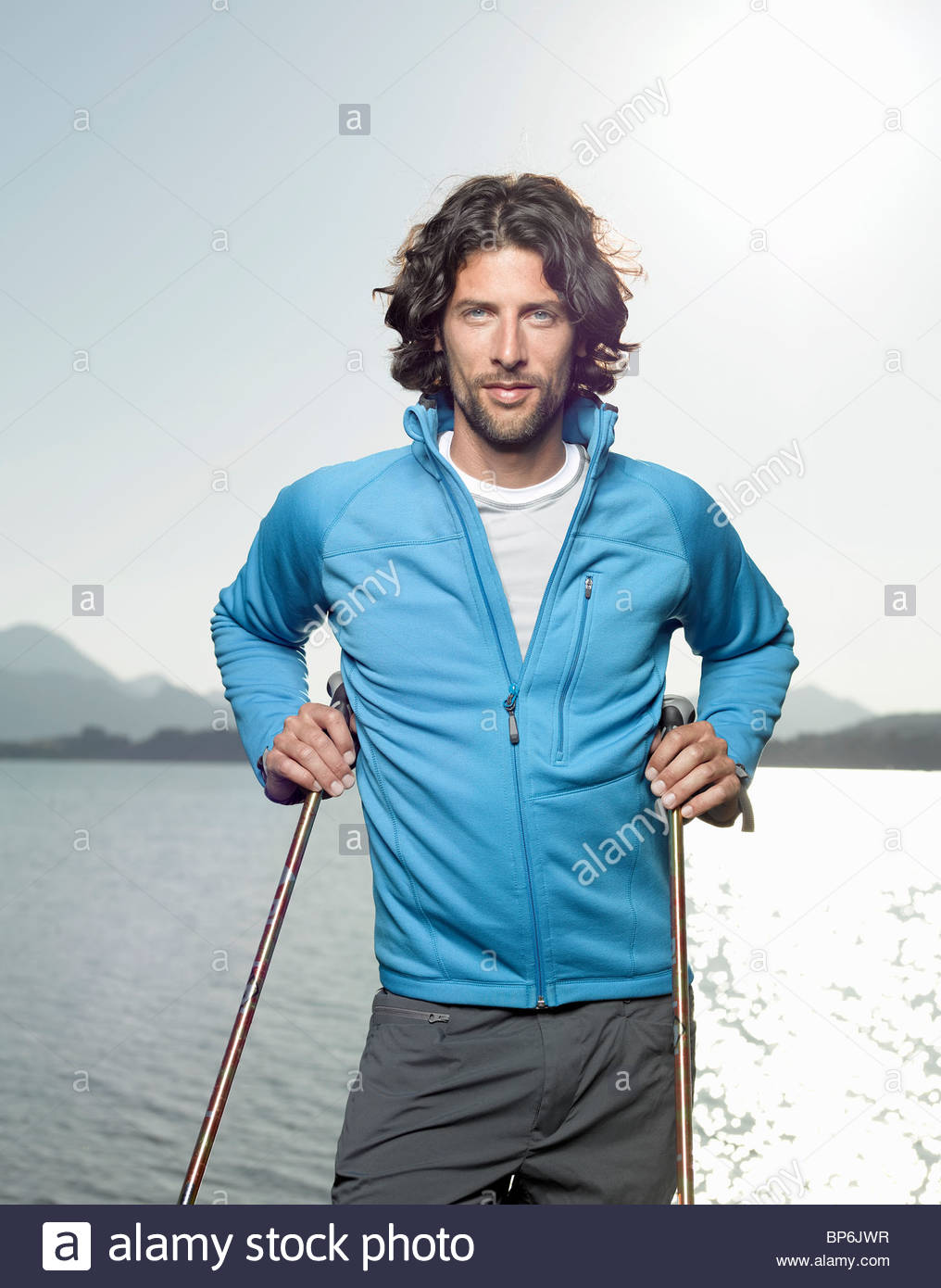 A young man beside a lake holding walking poles - Stock Image