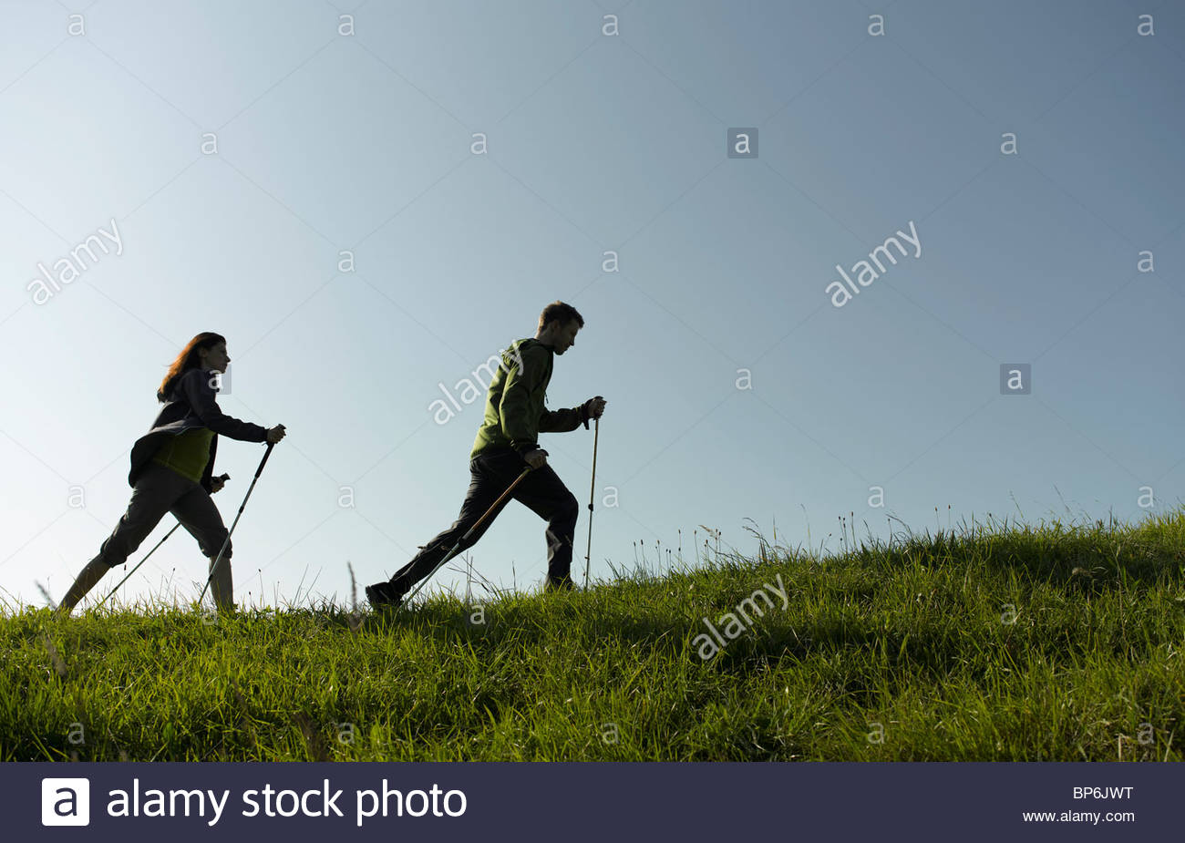 A couple out hiking, using walking poles - Stock Image