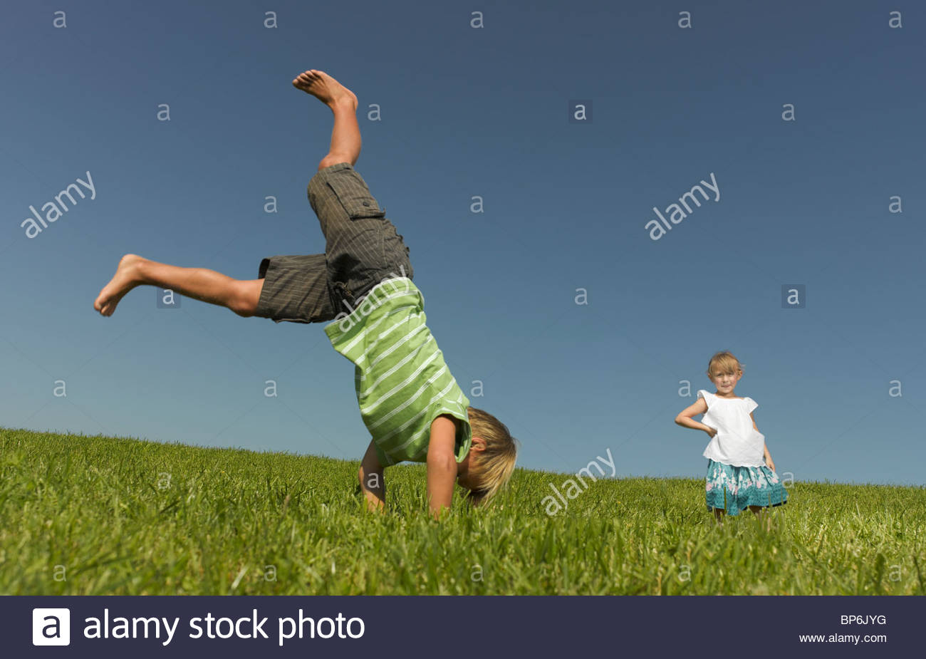 A young boy doing a handstand whilst his sister watches - Stock Image