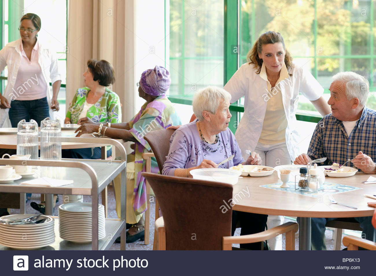 A group of senior people having lunch together in a retirement home - Stock Image