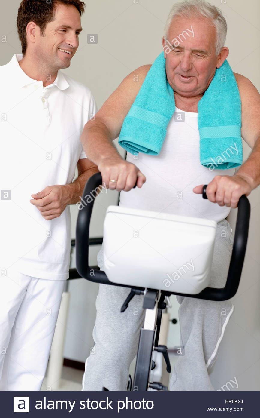 A senior man on an exercise bike, physiotherapist by his side - Stock Image