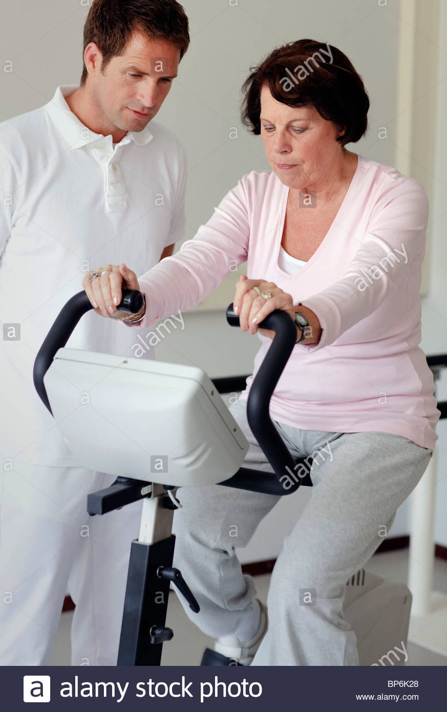 A senior woman on an exercise bike, physiotherapist by her side - Stock Image