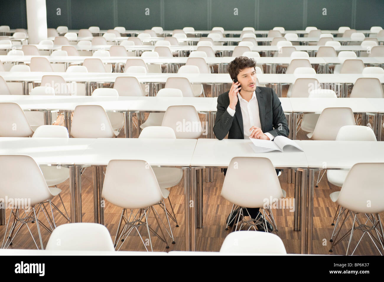 Businessman sitting at a cafeteria and talking on a mobile phone - Stock Image