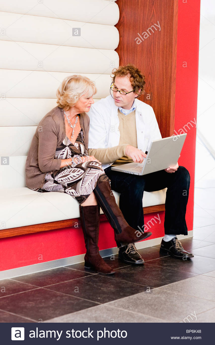 A senior woman with medical consultant looking at a laptop - Stock Image