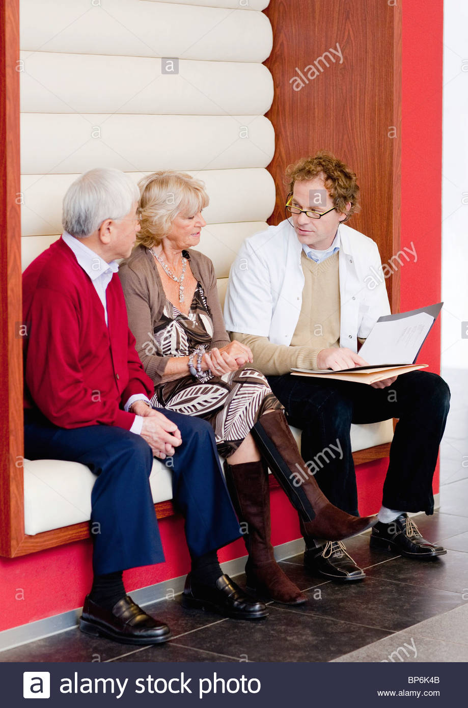 A senior couple talking to a medical consultant - Stock Image