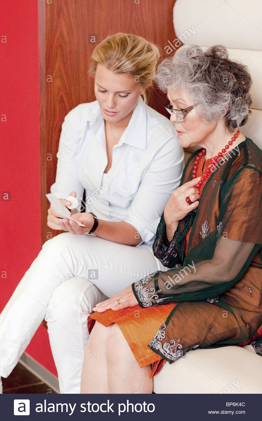 A medical consultant explaining medication to a senior woman - Stock Image