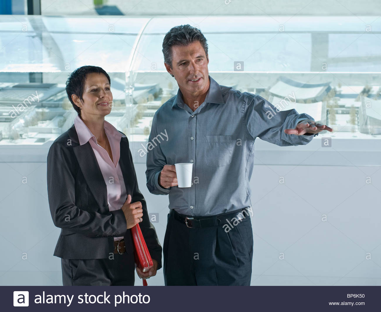 A businessman and businesswoman discussing architectural models - Stock Image