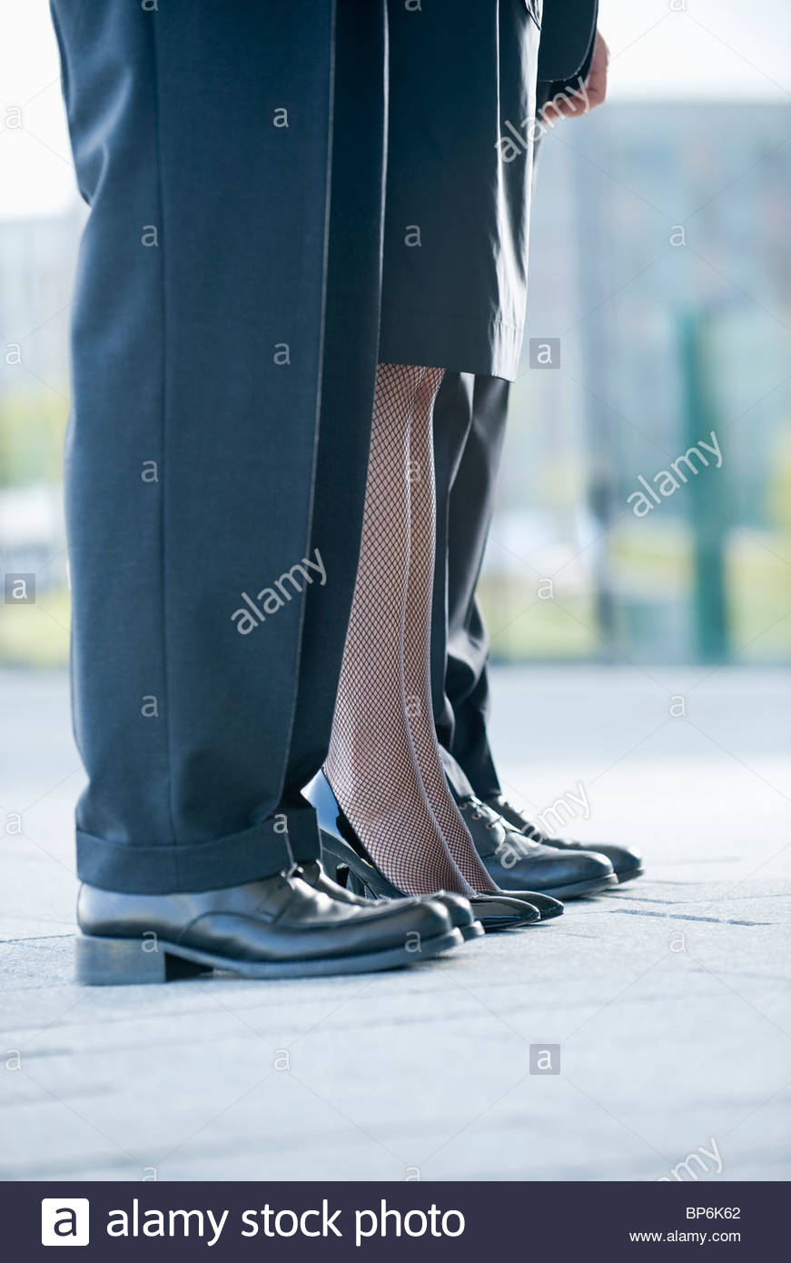 Two businessmen and a businesswoman standing in a row, close-up of their legs Stock Photo