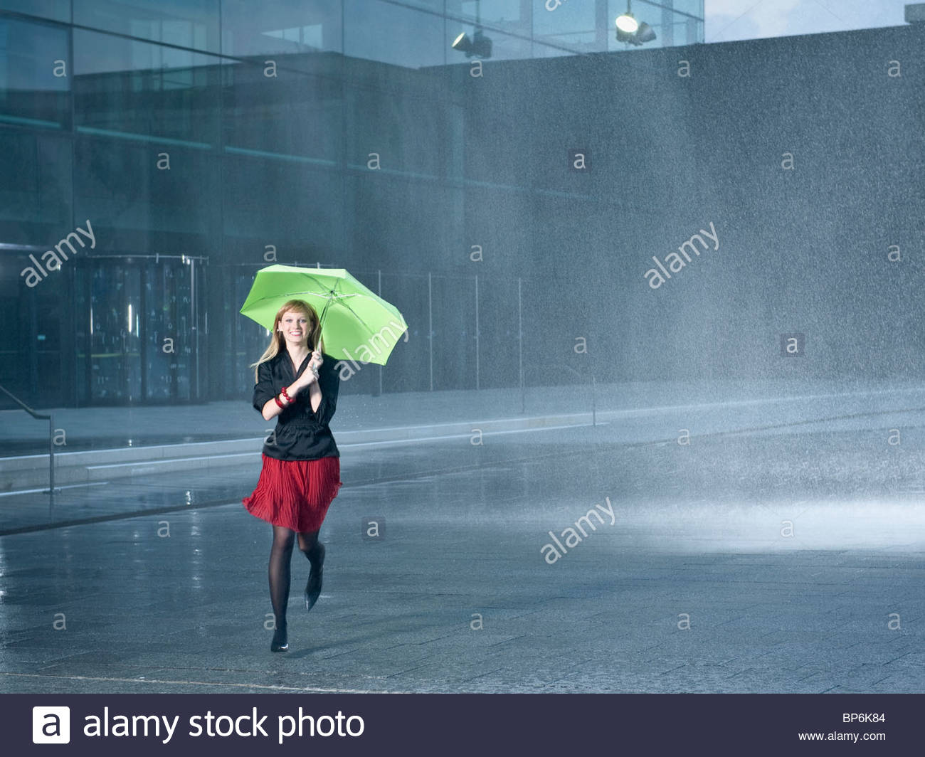 A young woman holding a green umbrella in the rain - Stock Image