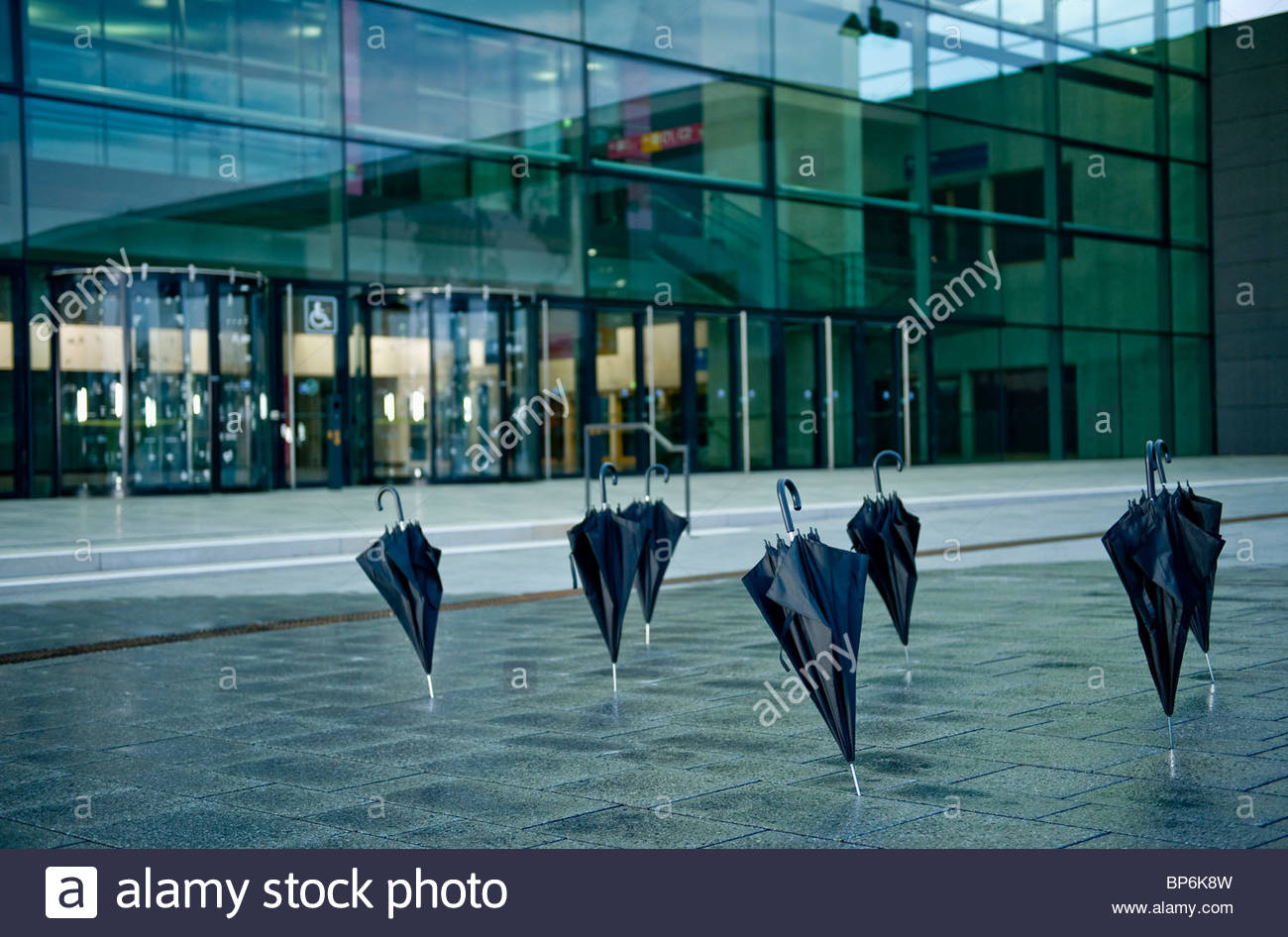 Black umbrellas standing upright outside a modern office building - Stock Image