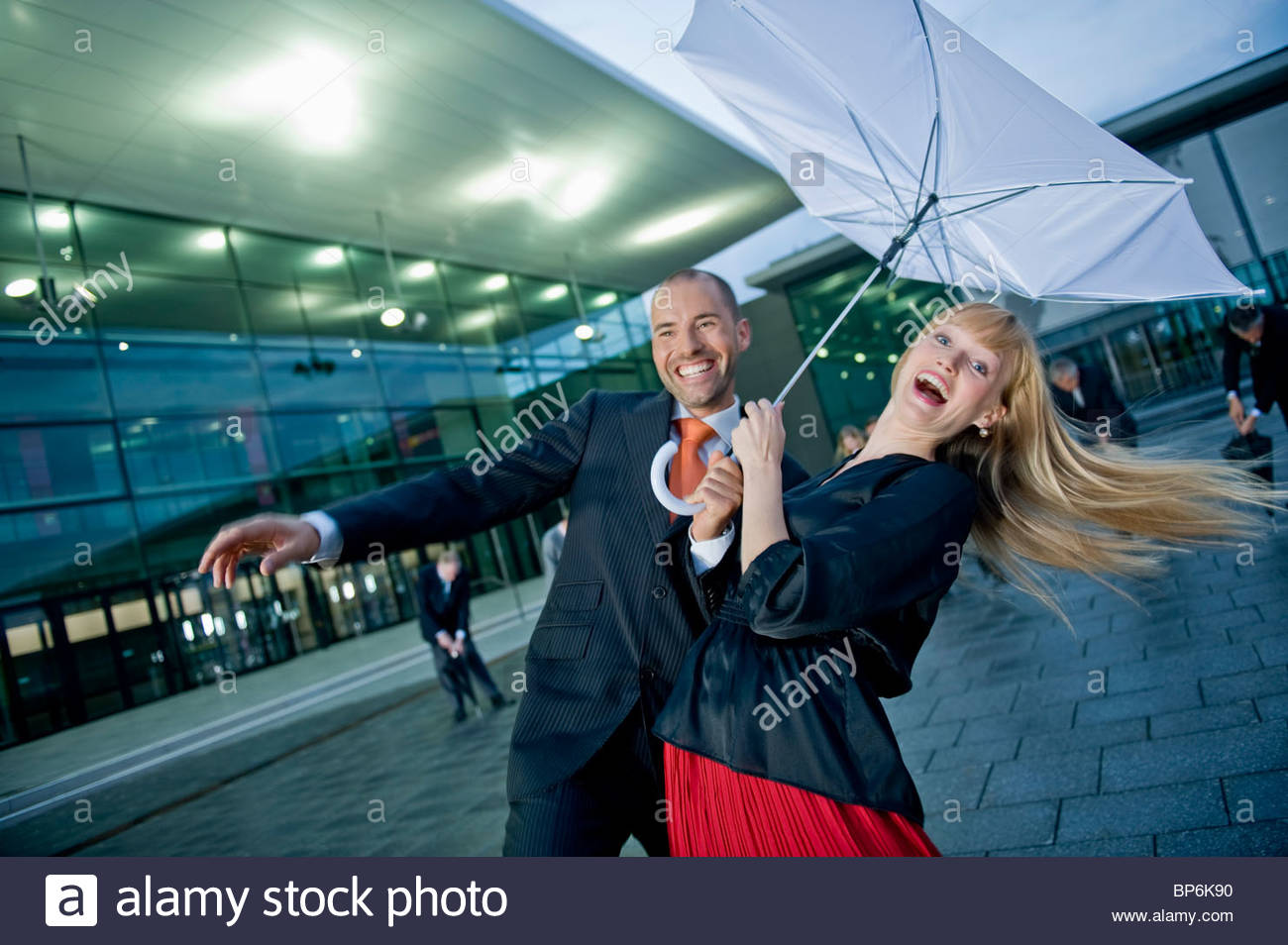 A businessman and businesswoman holding an umbrella in strong wind - Stock Image