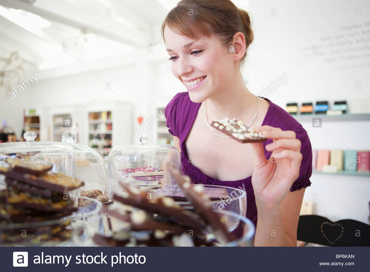 A woman choosing chocolate in a sweet shop - Stock Image