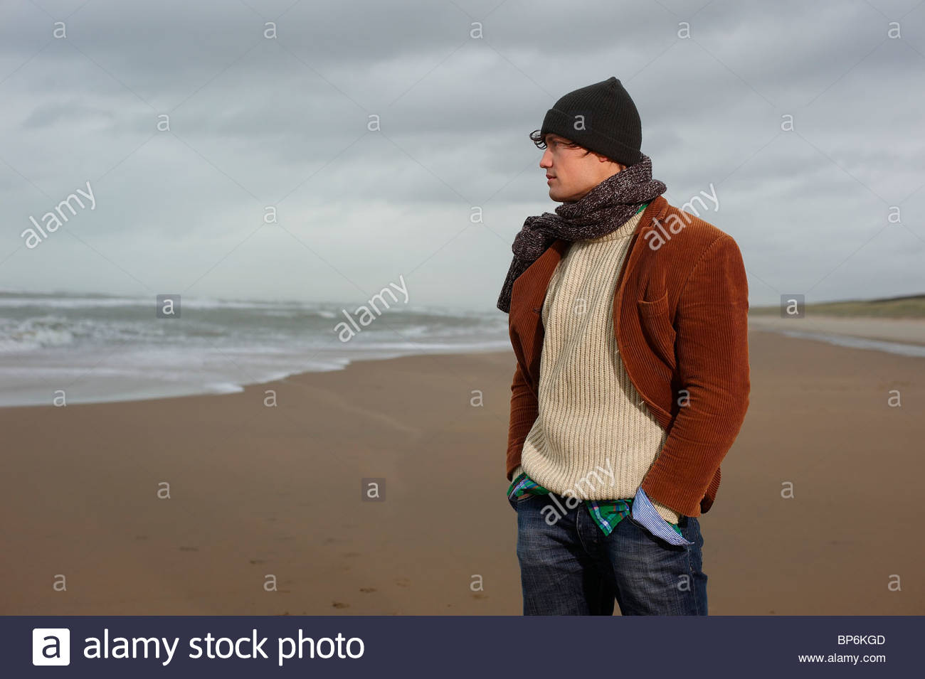A man standing on a beach on a winters day looking out to sea - Stock Image