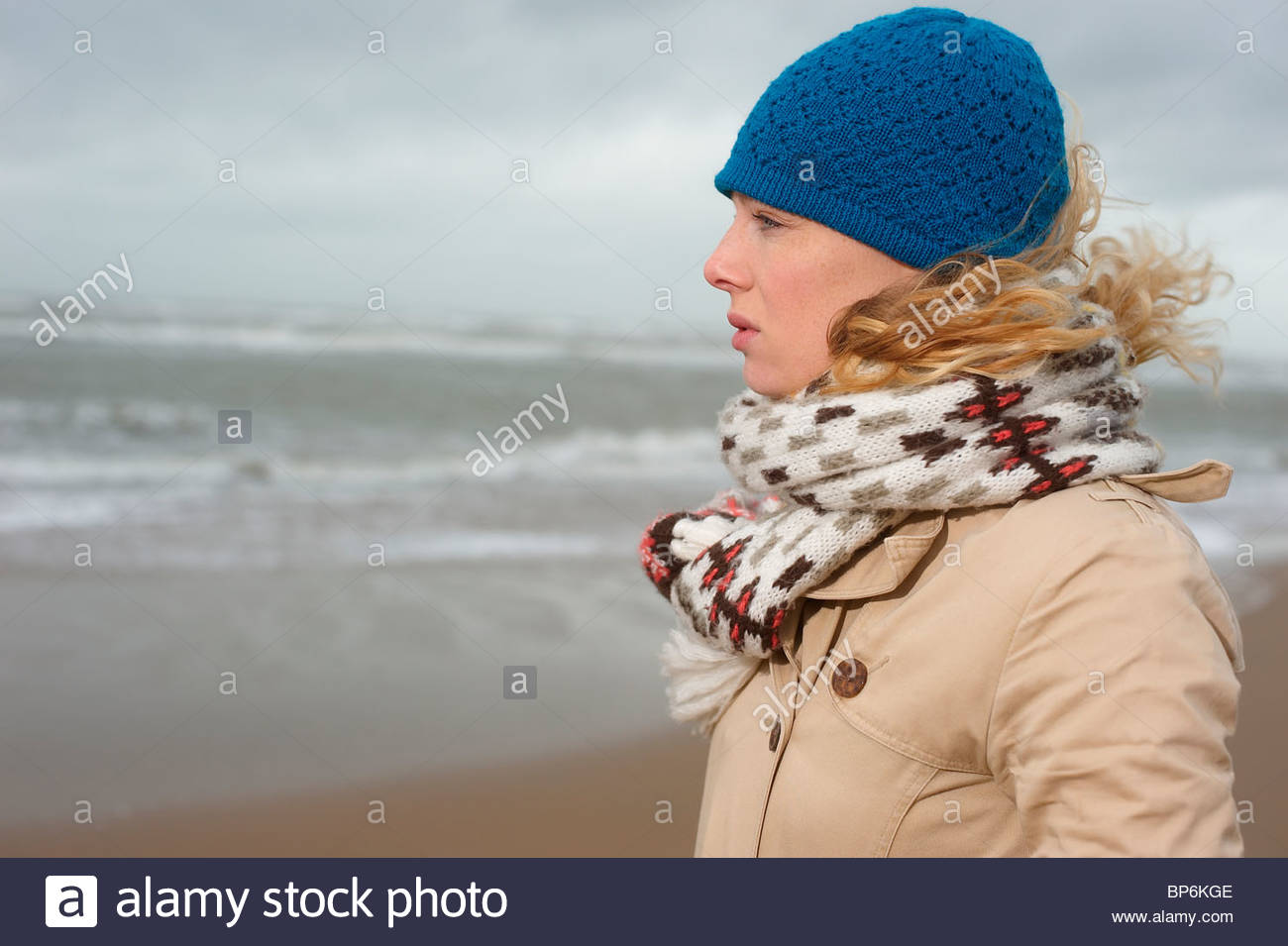 A woman looking out to sea on a winters day - Stock Image