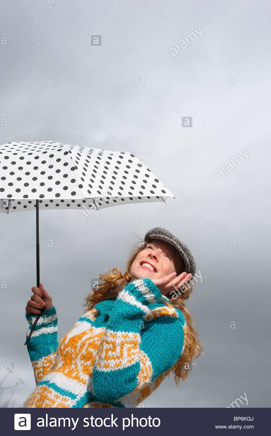 A woman holding a polka dot umbrella - Stock Image