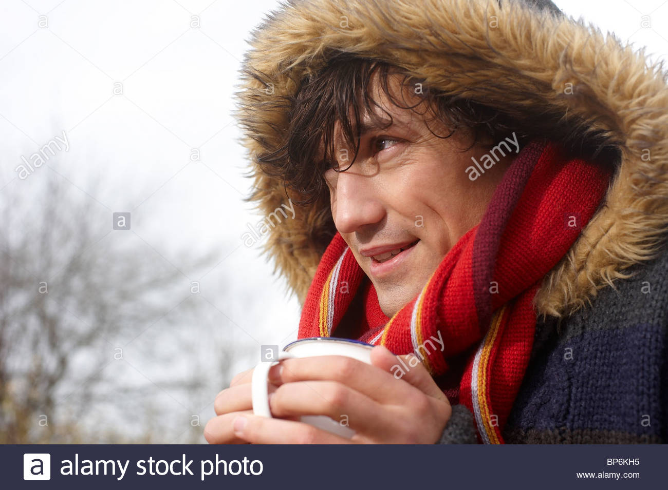 A mature man standing outdoors in winter time holding a hot drink - Stock Image
