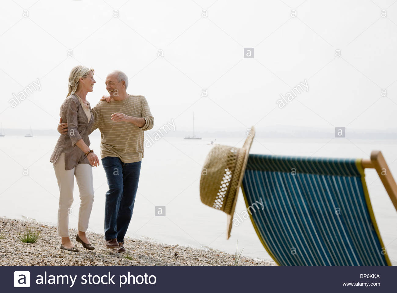 A senior couple walking beside a lake laughing - Stock Image