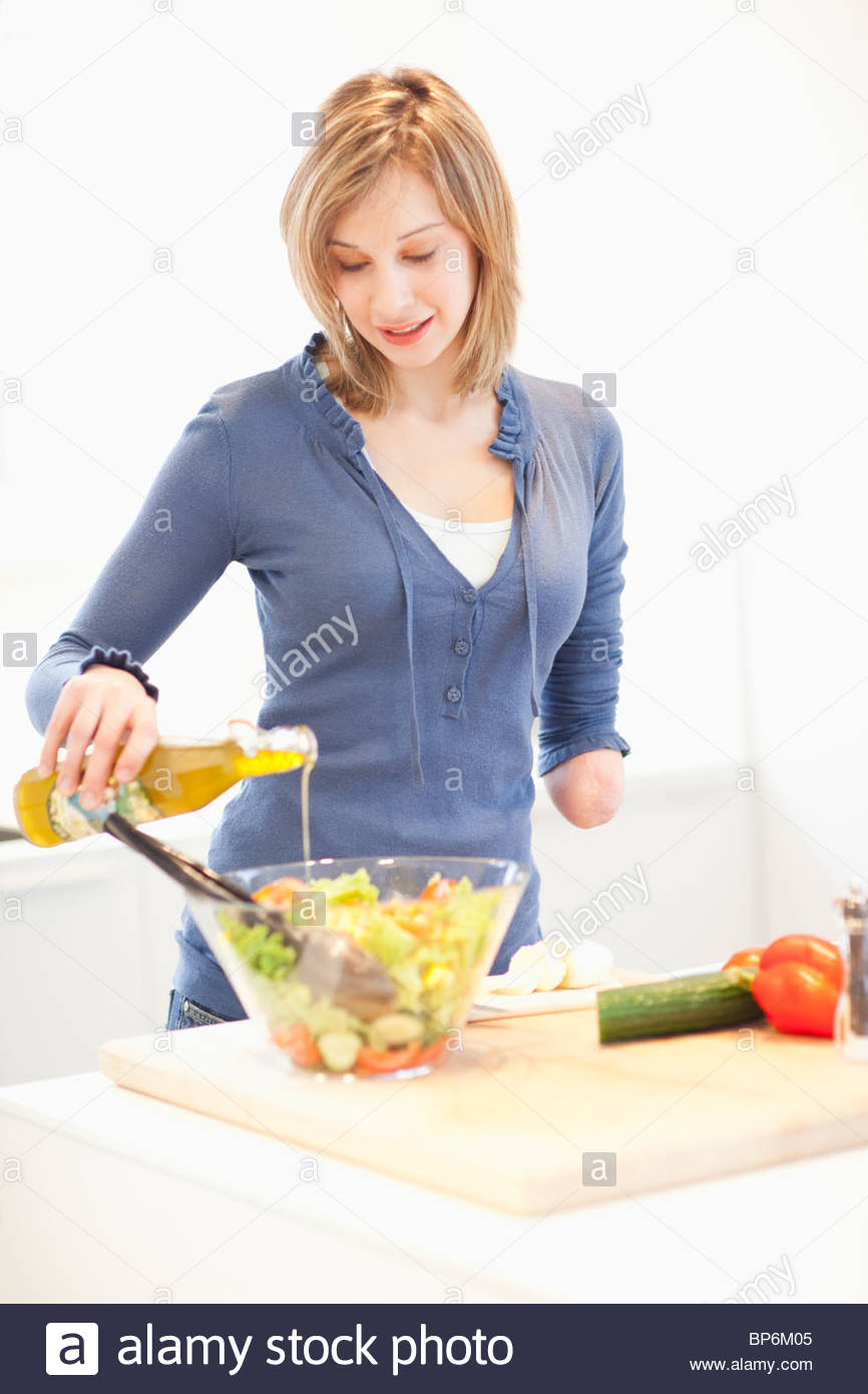 Young woman with amputee arm making salad in kitchen - Stock Image