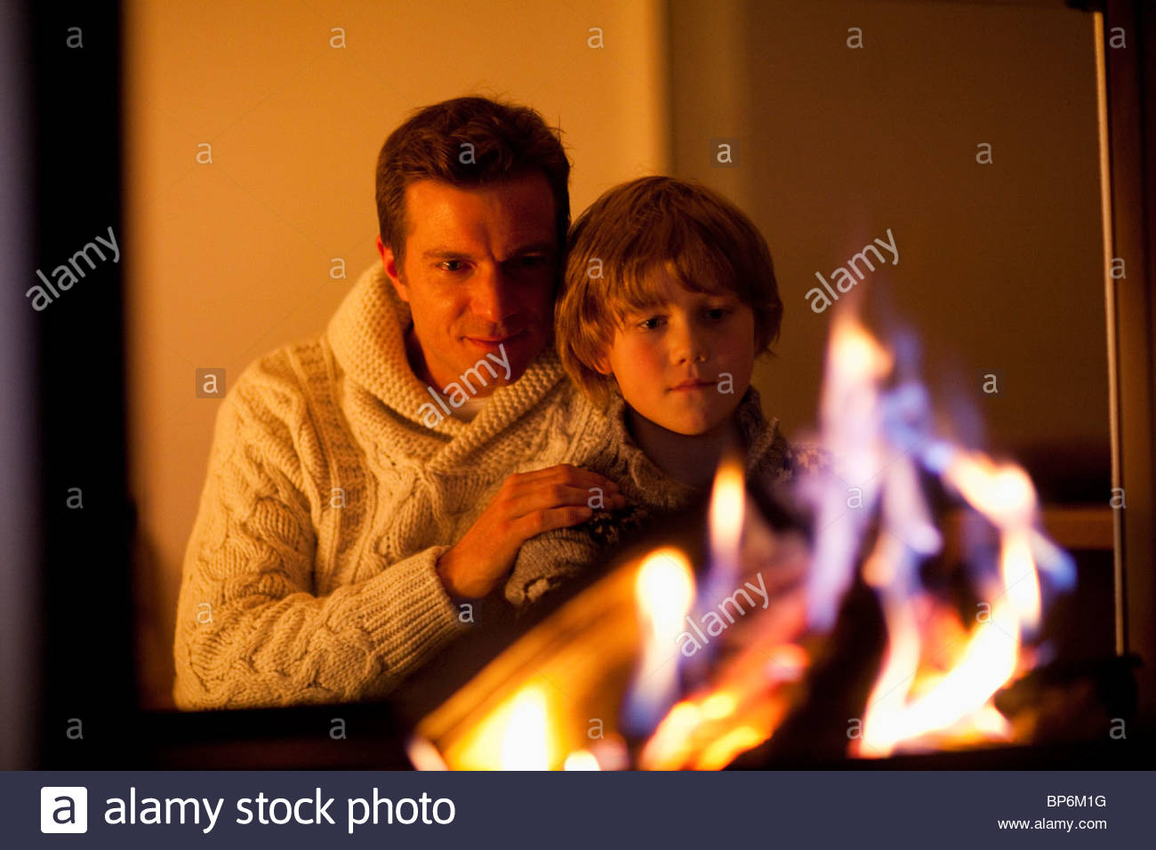 Father and son sitting near fireplace - Stock Image