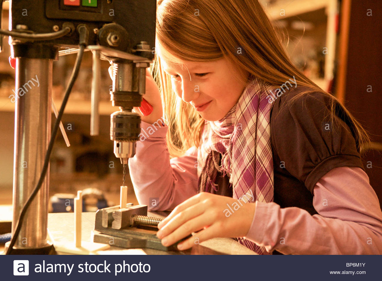Young girl using drill on craft she is making - Stock Image