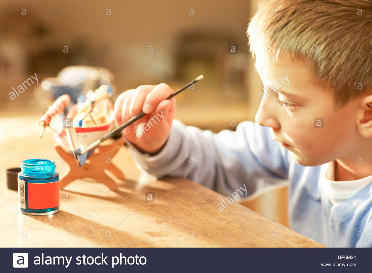 Young boy painting wooden craft - Stock Image