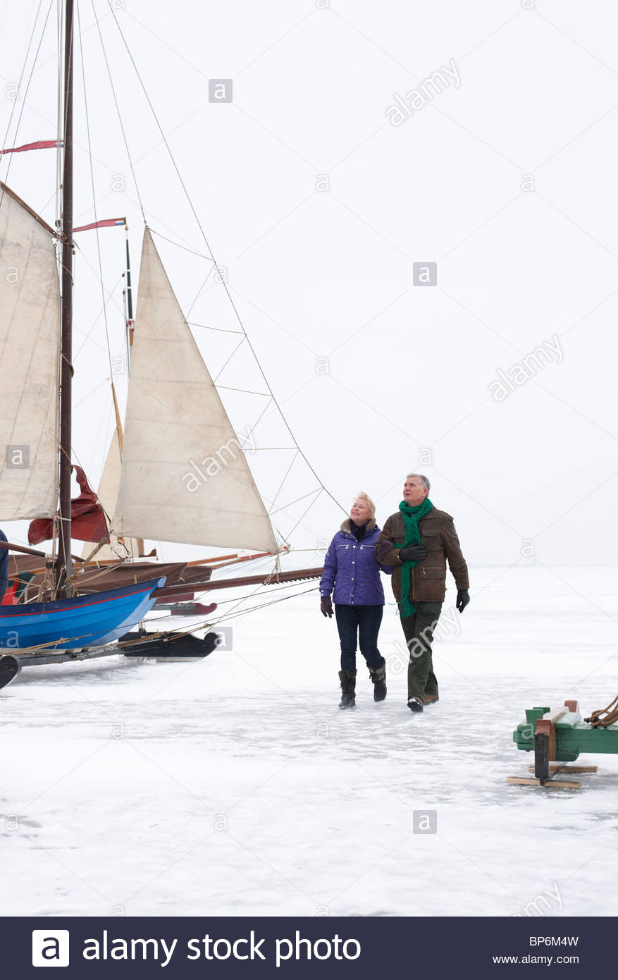 Senior couple walking on frozen lake near boats - Stock Image