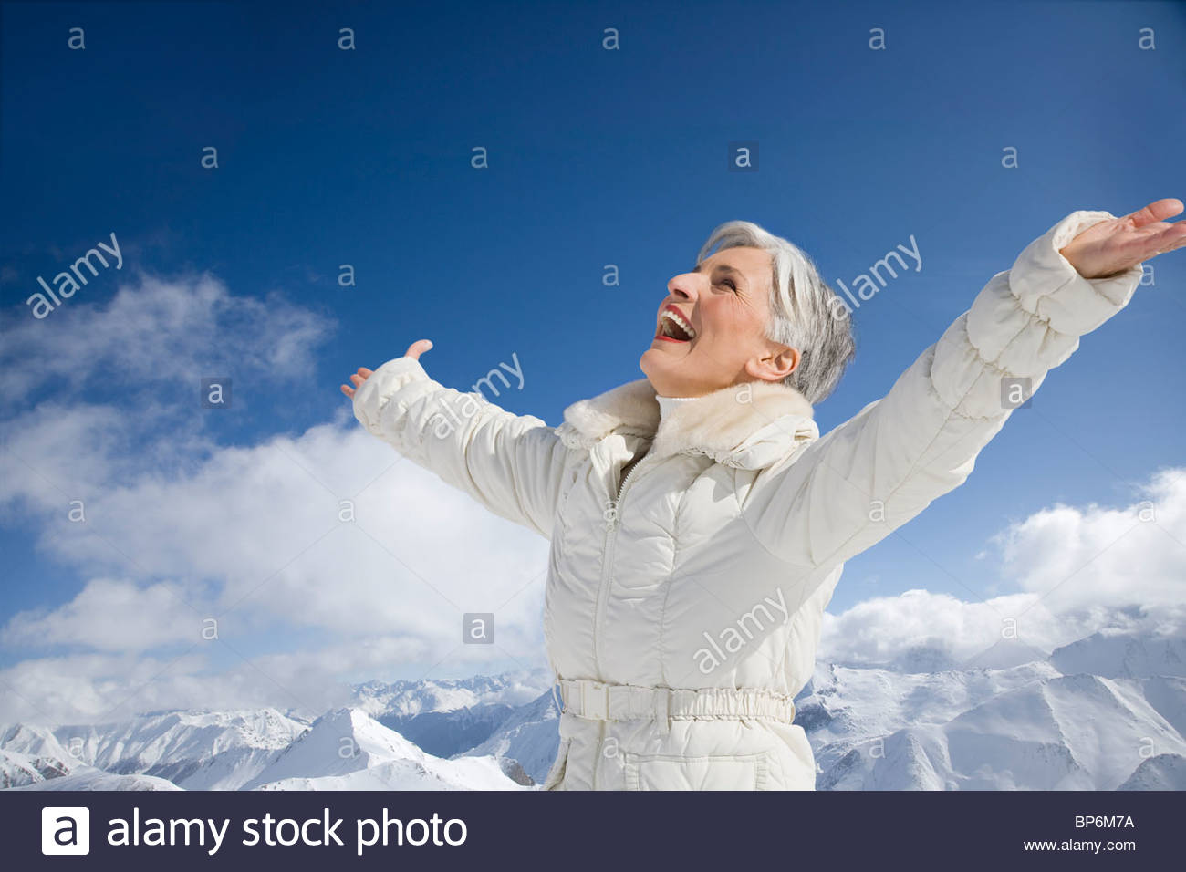 Mature woman with arms wide open on winter day - Stock Image